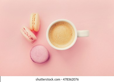 Cup of coffee with macaron on pink background from above, flat lay