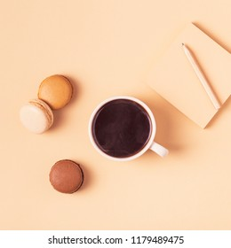 Cup of coffee with macaroons on pastel background, flat lay.