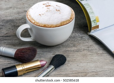 cup of coffee and make up kit on wooden table.
