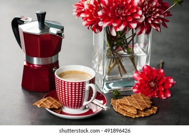 Cup of coffee with  coffee maker and flowers