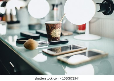 a cup of coffee and a make-up brush on the wizard's table in the backlight on a glass surface with blemishes
