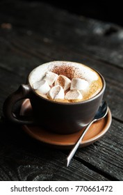cup of coffee with marshmallow on a dark wooden background