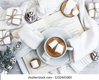 A cup of coffee with marshmallows stands on the open book. A warm sweater. New Year's and Christmas. Christmas tree and gifts of jewelry, bracelets with charms. Huggy concept.