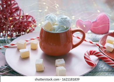 Cup of coffee with meringues and marshmallows, Turkish delight on a plate, hearts, illumination, against the background of a window, homeliness, Valentine's day