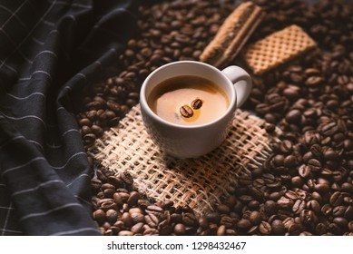 Cup of coffee in the middle of coffee beans with biscuits and tablecloth. Grained product. Hot drink. Close up. Harvesting. Natural background. Energy. Fresh espresso with beans on the foam.