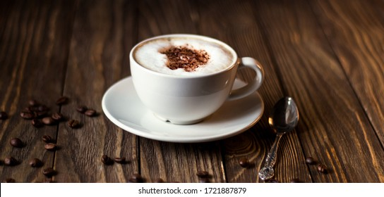 a Cup of coffee with milk and coffee beans on a dark wooden background. selective focus.