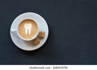Cup of coffee with milk, cane sugar and tooth sign on dark background. Top view. Copy space