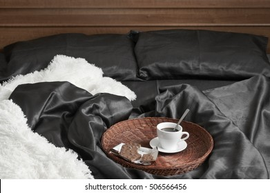 Cup of coffee and milk chocolate on wicker tray in bed with black satin linen and white shaggy plaid.