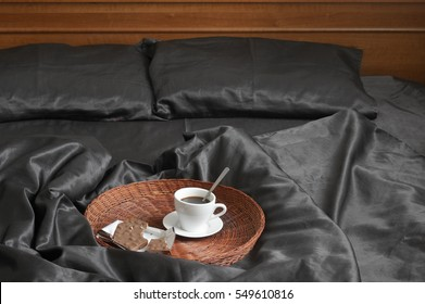 Cup of coffee and milk chocolate on wicker tray in bed with black satin linen and wooden bedhead.