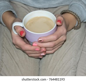 a cup of coffee with milk in female hands