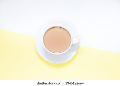 Cup of coffee with milk on a colored background, top view.