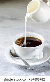 A cup of coffee with milk on a plate with a spoon. A stream of milk pours into the cup. Light concrete background