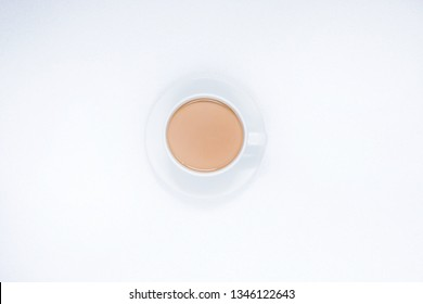 Cup of coffee with milk on a white background, top view.