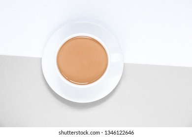 Cup of coffee with milk on white and grey background, top view.
