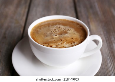 Cup of coffee with milk on wooden background