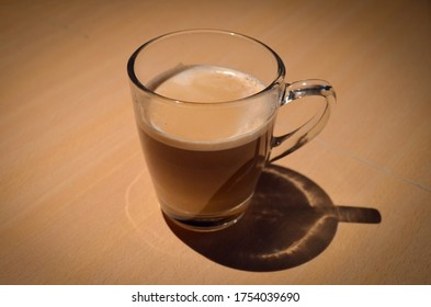 A cup of coffee with milk, over a wooden table. Smooth spot-light pointing to the cup. Morning ambience.