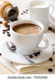 A cup of coffee with milk  pot on background