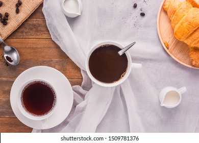 a cup of coffee with milk, sugar and croissant bread on wooden table, top view