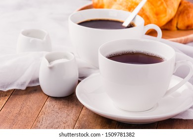 a cup of coffee, milk and sugar on wooden table