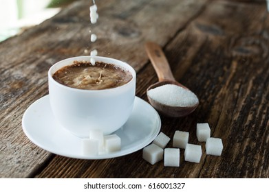 cup of coffee with milk and sugar spoon on the table