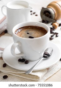 A cup of coffee with milkpot on background