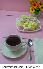 Cup of coffee in the morning on pink wooden table and delicious marshmallows. The concept of romatics breakfast, tenderness, good morning.