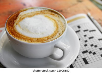 cup of coffee with morning paper, crossword puzzle