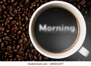 Cup of coffee with morning smoke and coffee beans on table with coffee beans.