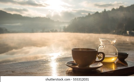 cup of coffee with mountain and river at morning sunrise.