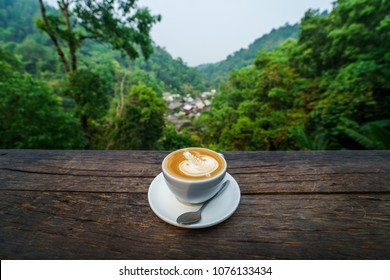A cup of coffee with mountain view background