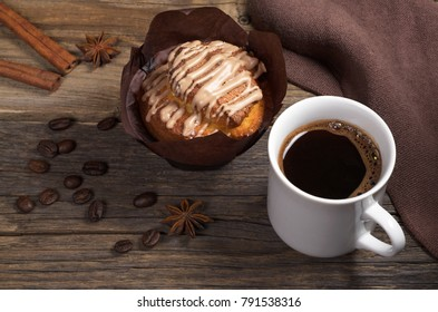 Cup of coffee and muffin with chocolate cream in brown wax paper on rustic wooden table close-up