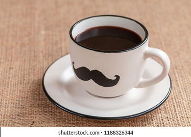 Cup of coffee with mustache on the burlap background. November concept. Prostate Cancer and men's health awareness. Funny party face