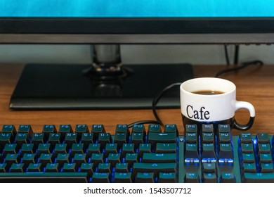 cup of coffee near a black keyboard with backlight on a wooden table