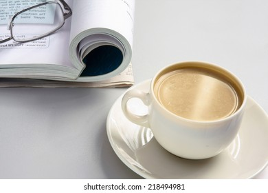 Cup of coffee near the book and glasses