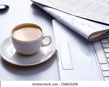 Cup of coffee near the laptop and newspapers