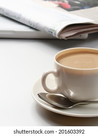 Cup of coffee near newspapers