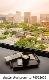 A cup of coffee near the window. In the distance is the panorama of Seoul, downtown, Deoksugung Palace. Anticipation, pleasure, joy.