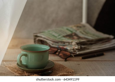 cup of coffee with a newspaper on the old desk.