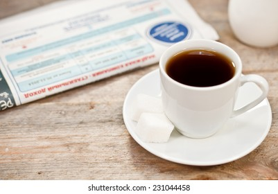 Cup of coffee and newspaper on a wooden table