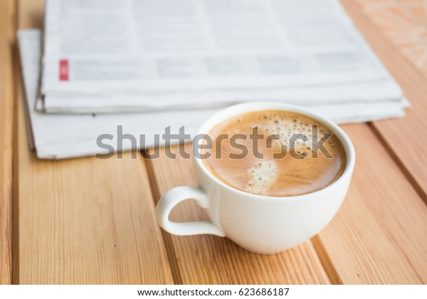 Cup of coffee and newspaper on the wooden table in the morning