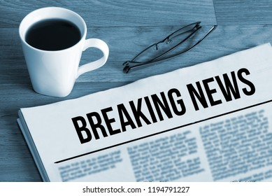 A cup of coffee and newspaper titled Breaking News