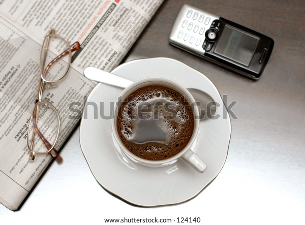 Cup of coffee, newspapers and glasses. Shallow depth of field intentional, focus on coffee.