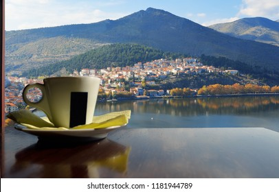 Cup of coffee next to window with view the town of  Kastoria in Greece