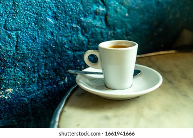 Cup of coffee in a nice hipster cafe. Soft focused image. Cup of espresso on old table of cafeteria.