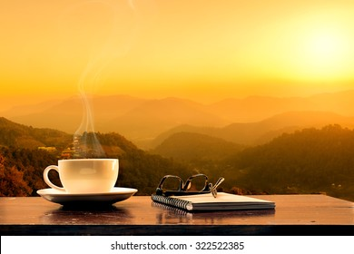 cup of coffee ,notebook and glasses with mountain at morning sunrise.
