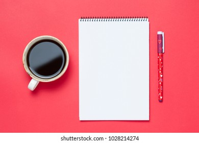 Cup of coffee and notebook on red background. Minimalistic style. top view, flat lay