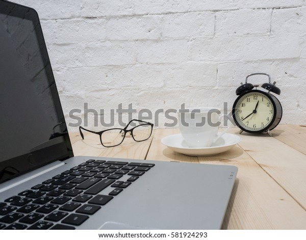 A cup of coffee and notebook on wood table . Coffee break in morning ,break working  / selective focus.Blank seating  indoor in living room .copy space for create idea for business.