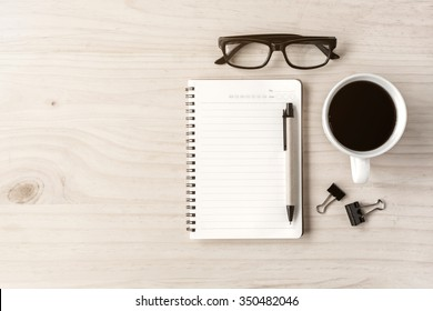 Cup of coffee with notebook on wooden desk, Top view, copy space