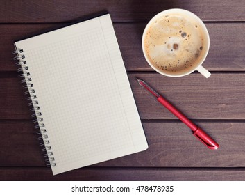 Cup of coffee with notebook on wooden desk. Top view