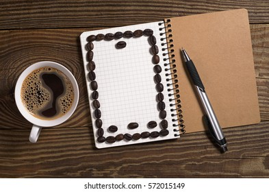 Cup of coffee and notebook with pen on old wooden background, top view